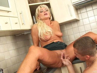 Blonde haired milf Sadie has sex with curious boy in the kitchen. This babe spreads her legs and gets her snatch licked and fingered by hot guy. This babe begs for love tunnel fucking after oral fun.
