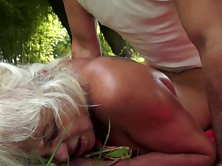 A blonde is on the grass on a towel, getting fucked in her cunt