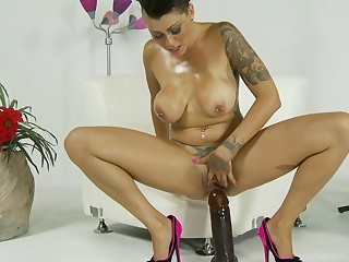 A busty lady is pushing a big cock shaped toy deep in her snatch