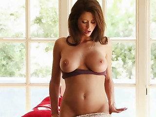 A bimbo with a pair of big boobs and a bald pussy is alone on the bed